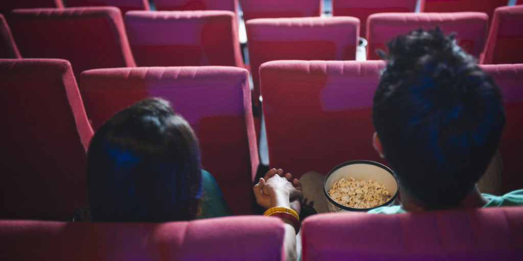 Couple enjoying movie with popcorns in a cinema hall